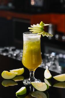 Zijaanzicht van groene appelcocktail versierd met sleced appels in een glas op bar achtergrond