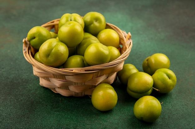 Zijaanzicht van groene pruimen in mand en op groene achtergrond