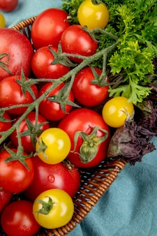 Zijaanzicht van groenten als basilicum van de tomatenkoriander in mand op blauwe doek