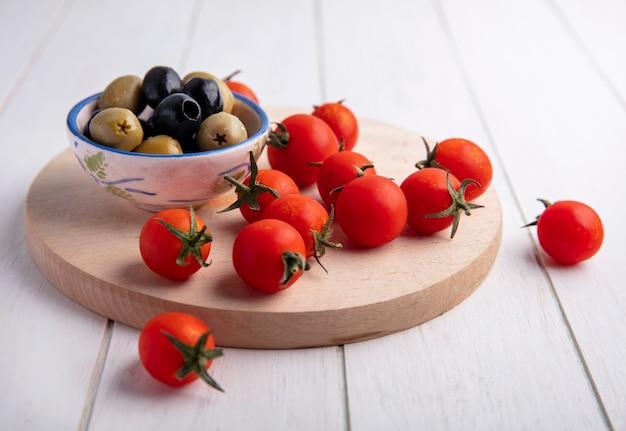 Zijaanzicht van groenten als kom met olijven en tomaten op snijplank op hout