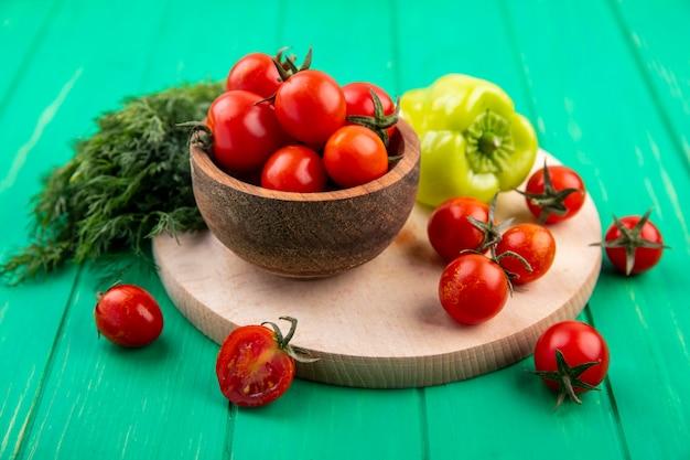 Zijaanzicht van groenten als kom tomaten en peper op snijplank met bos van dille op groen