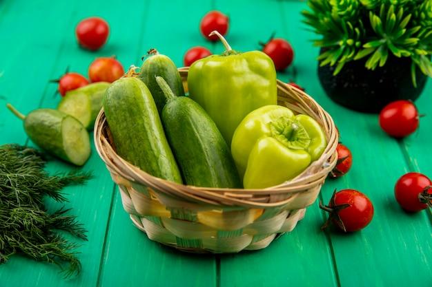 Zijaanzicht van groenten als peper en komkommer in mand met gesneden komkommer dille en tomaten op groen