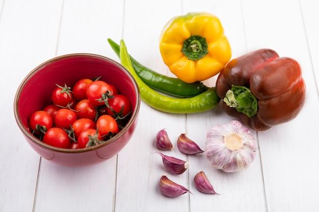 Zijaanzicht van groenten als tomaten in kom paprika knoflook bol en kruidnagel op hout