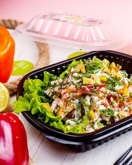 Zijaanzicht van groentesalade met de worteldille van paddestoelengroene paprika's en roomsaus in leveringsdoos