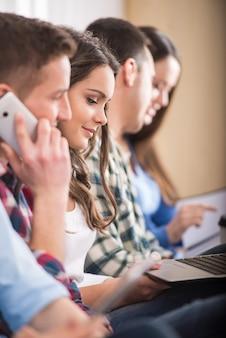 Zijaanzicht van groep studenten met laptop.