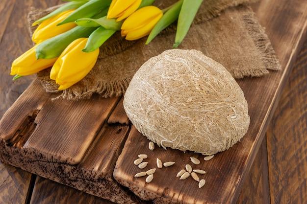 Zijaanzicht van halva, oosters zoet dessert gemaakt van pinda-olieachtige zaden vermalen tot een pasta en gemengd met suikersiroop geserveerd op houten bureau met bloemen.