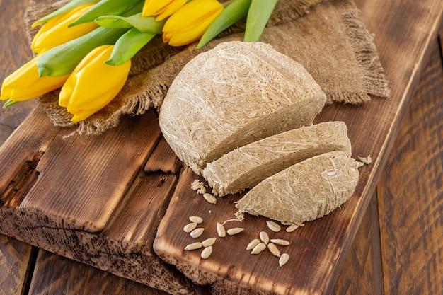 Zijaanzicht van halva, oriëntaals zoet dessert gemaakt van pinda-olieachtige zaden vermalen tot een pasta en gemengd met suikersiroop geserveerd op houten bureau met bloemen.