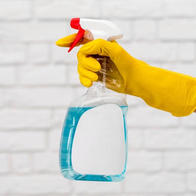 Zijaanzicht van hand met de schoonmakende oplossing van de handschoenholding