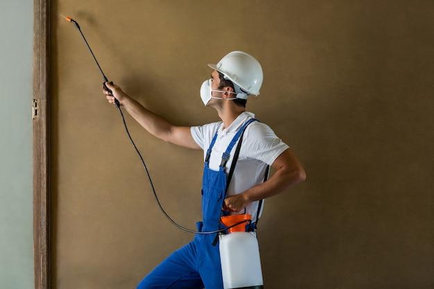 Zijaanzicht van handarbeiders bespuitend chemisch product op muur