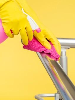 Zijaanzicht van handen met chirurgische handschoenen die leuning met doek en wassing schoonmaken