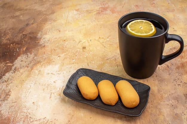 Zijaanzicht van handen met zwarte thee in een kopje met citroen op gemengde kleurentafel