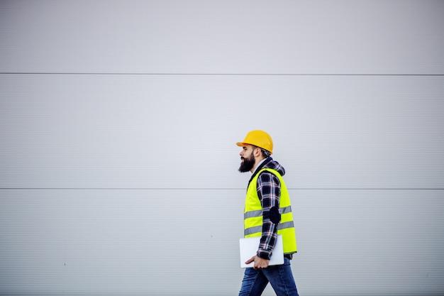 Zijaanzicht van hardwerkende bouwvakker met veiligheidshelm op hoofd en vest met laptop in handen en haasten op de bouwplaats.