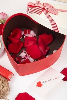 Zijaanzicht van hartvormige die giftdoos met rode roze bloemblaadjes op witte achtergrond wordt gevuld
