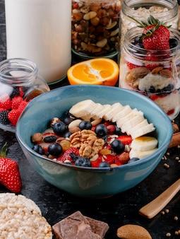 Zijaanzicht van havermoutpap met aardbeien, bosbessen, bananen, gedroogd fruit en noten in een keramische kom op tafel