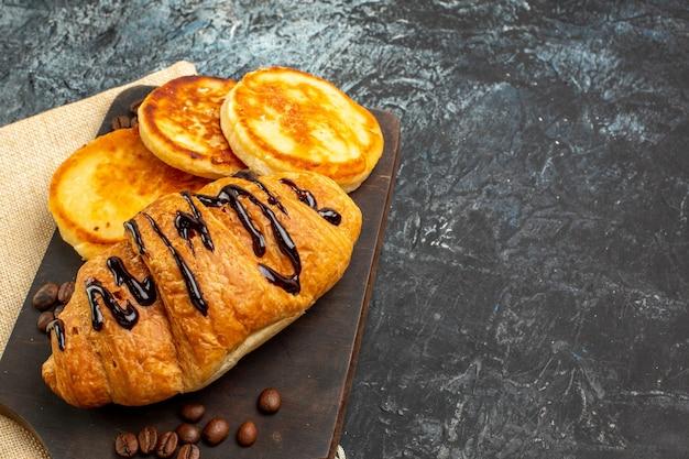 Zijaanzicht van heerlijke croissantpannenkoeken op houten snijplank voor geliefde aan de rechterkant op donkere ondergrond
