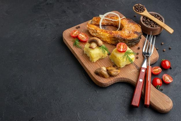 Zijaanzicht van heerlijke gebakken vis en champignons tomaten groenen op houten snijplank bestekset peper op zwarte ondergrond
