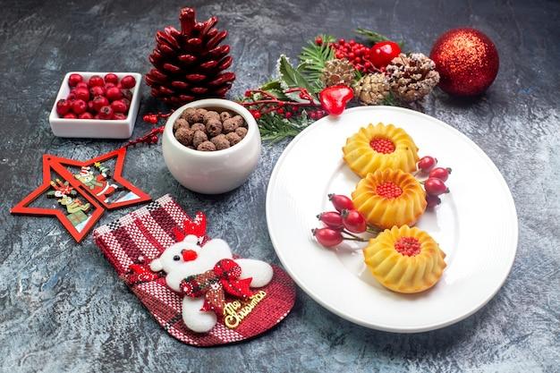 Zijaanzicht van heerlijke koekjes op een witte plaat santa claus sok en cornell in een kom dennentakken op donkere ondergrond