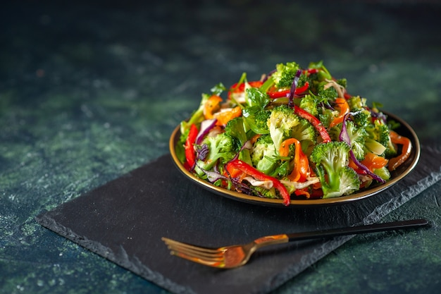 Zijaanzicht van heerlijke veganistische salade met verse ingrediënten in een bord en vork op zwarte snijplank op blauwe achtergrond