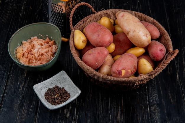 Zijaanzicht van hele aardappelen in mand en geraspte degenen in kom met zwarte peper zaden en rasp op houten tafel