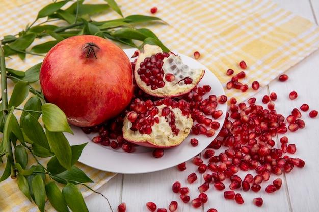 Zijaanzicht van hele granaatappel en granaatappelstukken met bessen in plaat en bladeren op geruite doek met granaatappelbessen op hout