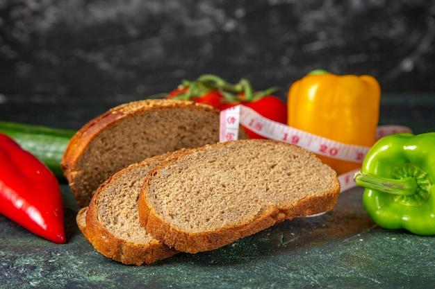 Zijaanzicht van hele verse biologische groenten en zwarte sneetjes brood