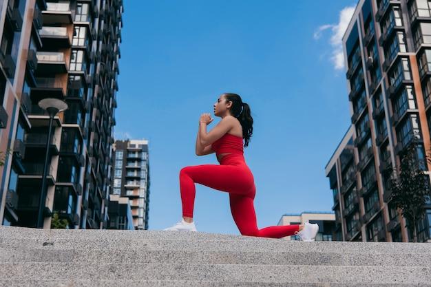 Zijaanzicht van het concentreren van sportieve blanke vrouw gekleed in rode sportkleding en witte sneakers en met paardenstaart lunges doen.
