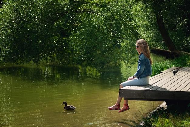Zijaanzicht van het dromen meisjeszitting op houten pijler op rivierbank. mooie vrouw met haar geblazen met de wind.