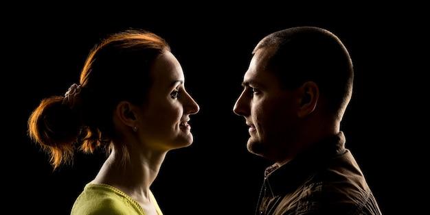 Zijaanzicht van het gezicht van de vrouw en het gezicht van de man ondersteboven over zwart