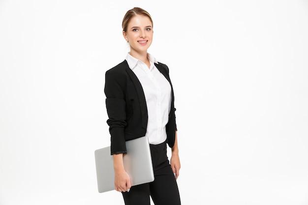 Zijaanzicht van het glimlachen het blonde bedrijfsvrouw stellen in studio met laptop computer ter beschikking en over witte muur