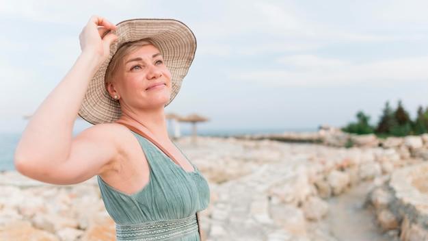 Zijaanzicht van het hogere toeristenvrouw stellen met strandhoed