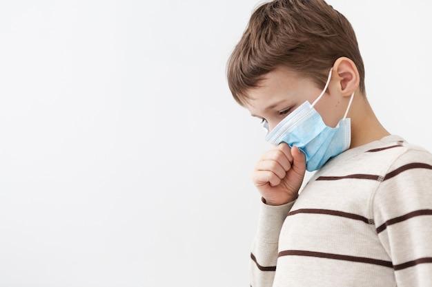 Zijaanzicht van het kind met medische masker hoesten