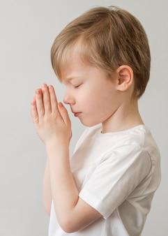 Zijaanzicht van het kleine jongen bidden