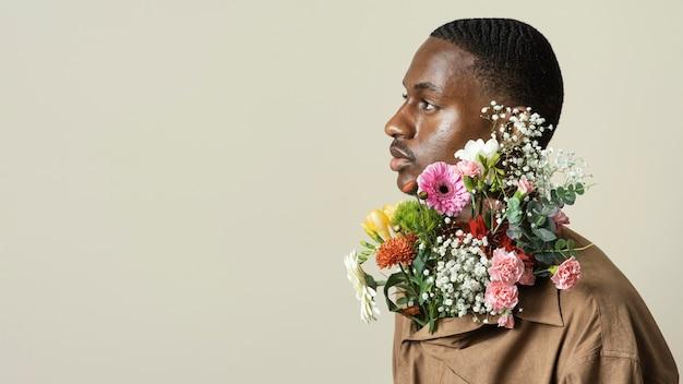 Zijaanzicht van het knappe man poseren met boeket bloemen en kopieer de ruimte
