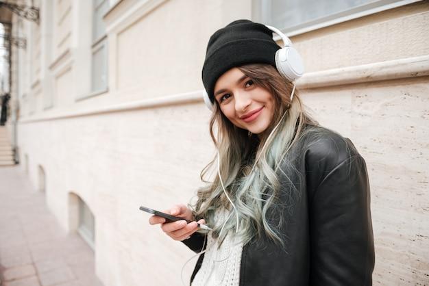 Zijaanzicht van het luisteren van de vrouw muziek op de straat