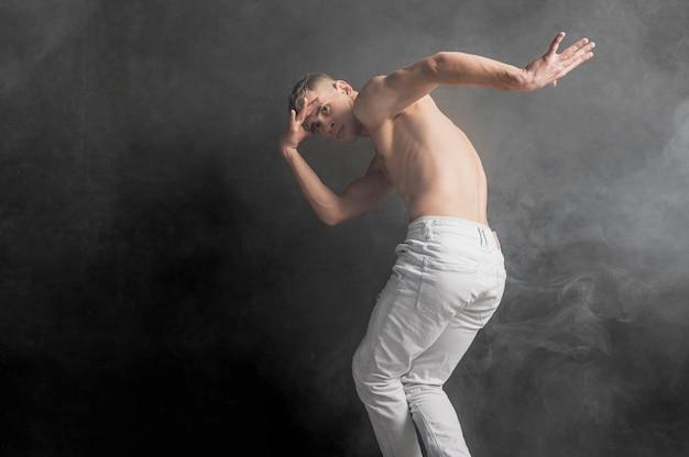 Zijaanzicht van het mannelijke danser stellen in jeans met mist en exemplaarruimte
