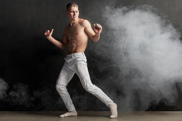 Zijaanzicht van het mannelijke uitvoerder stellen in jeans met rook en exemplaarruimte