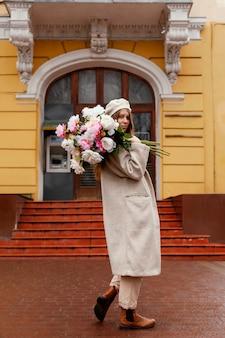 Zijaanzicht van het mooie boeket van de vrouwenholding bloemen