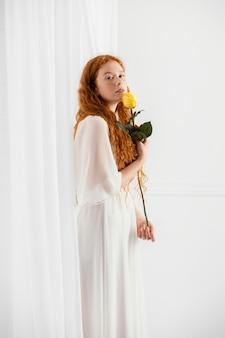 Zijaanzicht van het mooie vrouw stellen met een de lentebloem