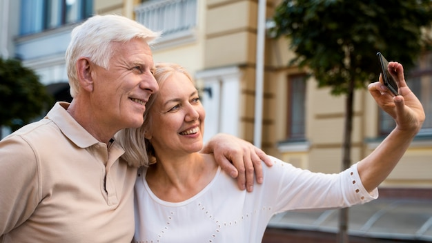 Zijaanzicht van het oudere paar smiley buitenshuis een selfie te nemen