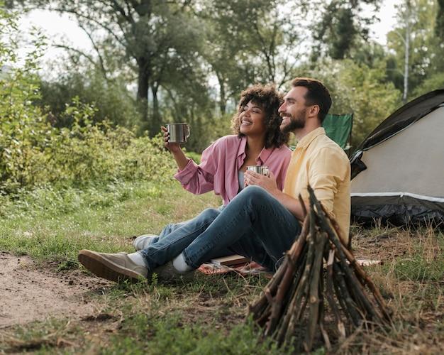 Zijaanzicht van het paar dat van het uitzicht geniet tijdens het kamperen