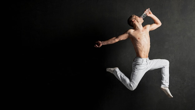 Zijaanzicht van het shirtless mannelijke danser stellen in mid-air met exemplaarruimte