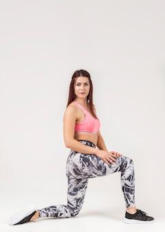 Zijaanzicht van het sportieve vrouw stellen in gymnastiekkleren