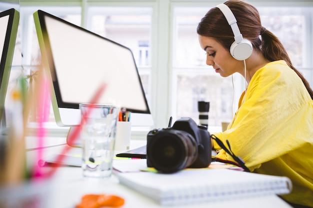 Zijaanzicht van het uitvoerende werken met camera aan bureau op creatief kantoor