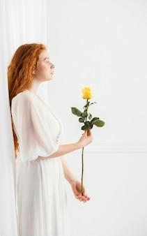 Zijaanzicht van het verleidelijke vrouw stellen met een de lentebloem en exemplaarruimte