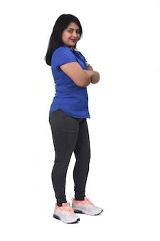 Zijaanzicht van het volledige portret van een latijns-vrouw gekruiste armen en kijken naar camera op witte achtergrond