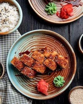 Zijaanzicht van hete gebakken sushi rolt met zalm avocado en kaas geserveerd met gember en wasabi op een bord op houten tafel