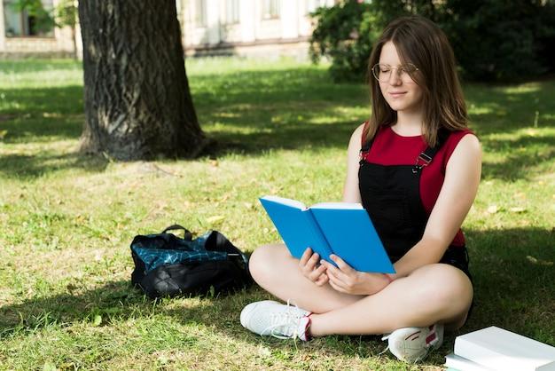 Zijaanzicht van highschool meisje leesboek
