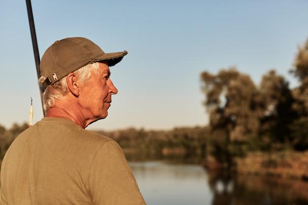 Zijaanzicht van hogere mensenzitting op bank van rivier en opzij kijkend, hebbend rust in openlucht, genietend van mooie aard dichtbij meer, dragend groene t-shirt en glb.