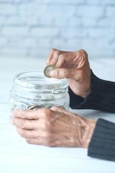 Zijaanzicht van hogere vrouwenhand die muntstukken in een kruik besparen