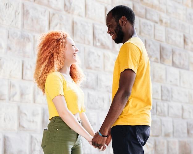Zijaanzicht van interraciale paar hand in hand